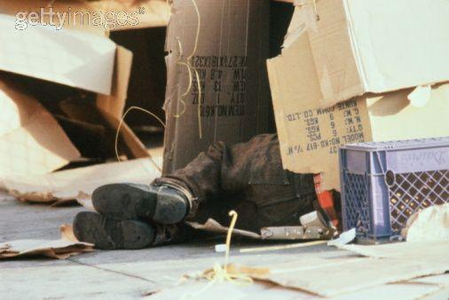 homeless person sleeping in cardboard box